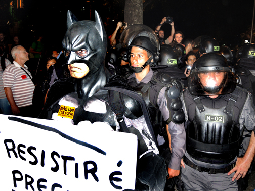 Batman stands his ground calling for resistance in front of a pack of Policia Militar