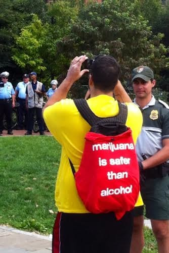 4/20 marijuana legalization protester photographs police on the lookout for drug users at Philadelphia's Liberty Bell protest