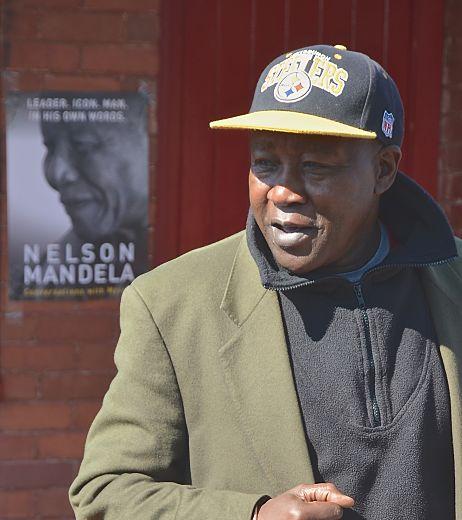 Ngugi Githuka talks with tourists outside Mandela House Museum. LBWPhoto