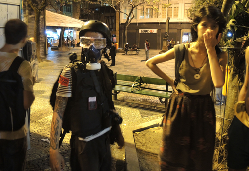 A young Cariocan with gas mask and his friend watch arrests being made.