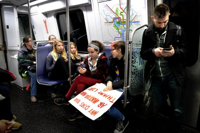 The Future checking their iphones on the Metro after the march