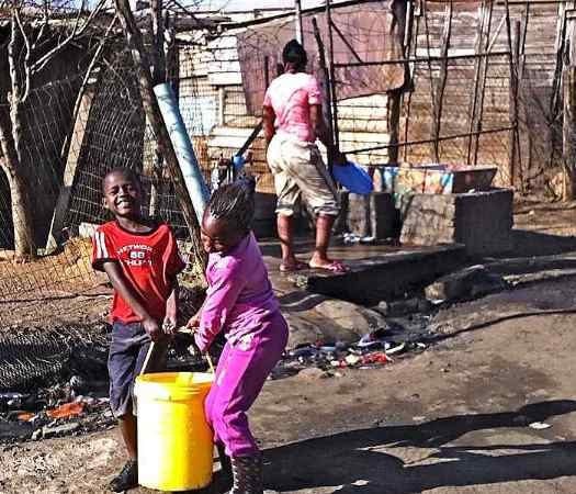 Children carry water from a communal faucet in the Kliptown shantytown adjacent to Soweto. Most dwellings in Kliptown lack water