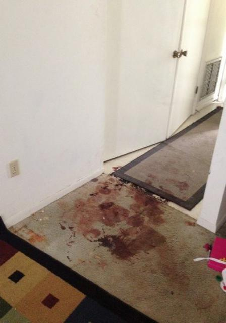 Close-up view of the exit from the living area to the foyer leading to the front door, showing the blood in the area where the f