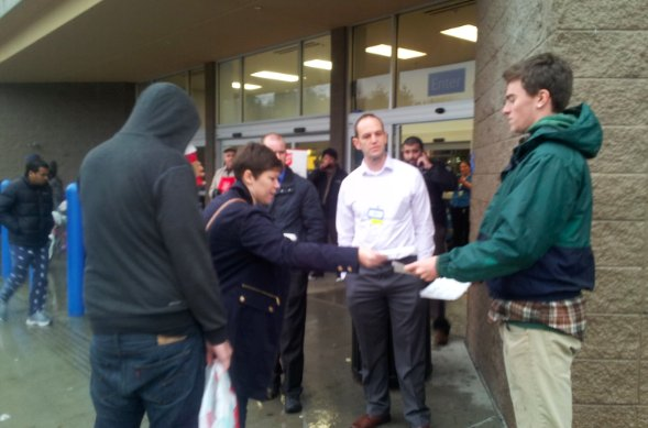 Striking Walmart worker hands out information about the nation's largest employer and its exploitive labor practices