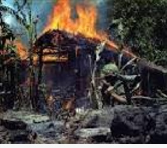 US soldier uses a flame thrower to torch a Vietnamese peasant hut